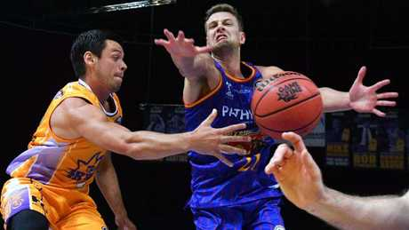 Kings player Jason Cadee (left) passes the ball past 36ers player Daniel Johnson on Saturday night.