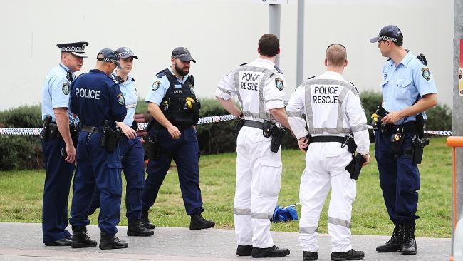Police scour the area outside Hurstville Train Station for clues.