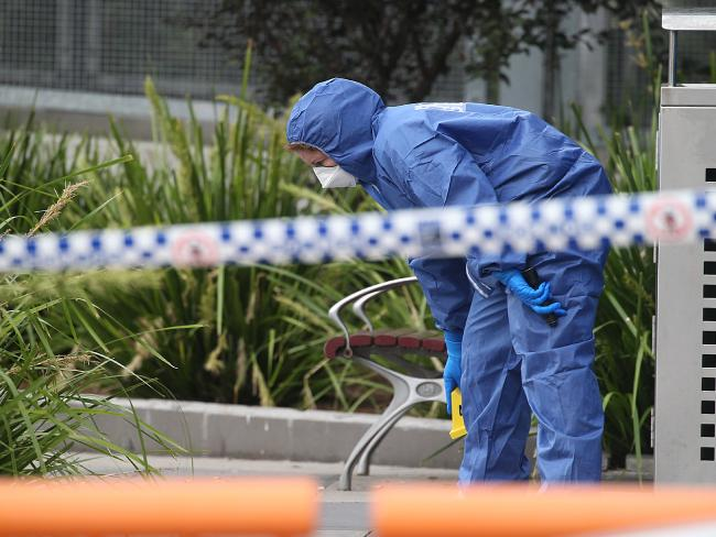 A forensic searches for clues outside Hurstville Train Station.