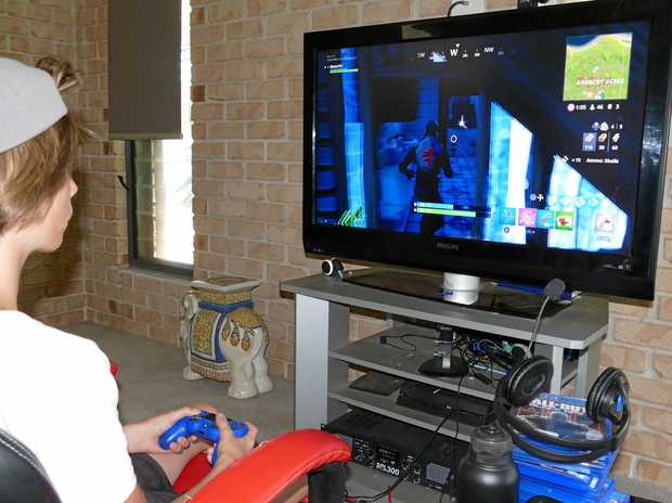 HARD AT IT: Grafton teenager Jack Murray keeps polishes his skills on the online computer game Fortnite. He has reached a world ranking of 23 in one online game and is looking to make a career in gaming. INSET: A screen shot of the game Fortnite.