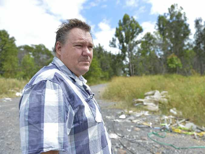 CLEAN IT UP: Ipswich resident Darren Butcher is disgusted by the volume of rubbish dumped at a Riverview property, next to a school.