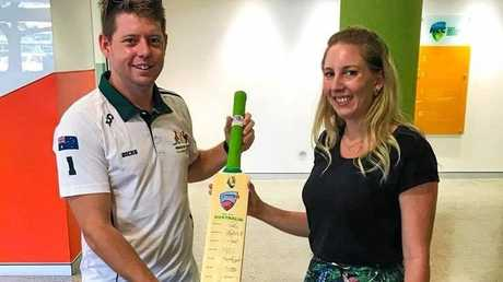 Organiser of Smack My Pitch Up Cricket, Tommy Watkins, collecting a signed bat from Cricket Australia manager Louise, set to be auctioned off with proceeds going to Soldier On