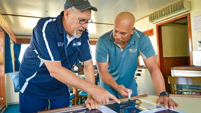 WORKING TOGETHER: Bruce Stobo, skipper and owner of Kanimbla, looks over aerial photos of the reef to work out the best places to drop anchor with Sacha Taylor from QPWS.