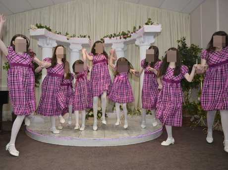 Nine of the Turpin sisters in matching pink plaid dresses jump for the camera.