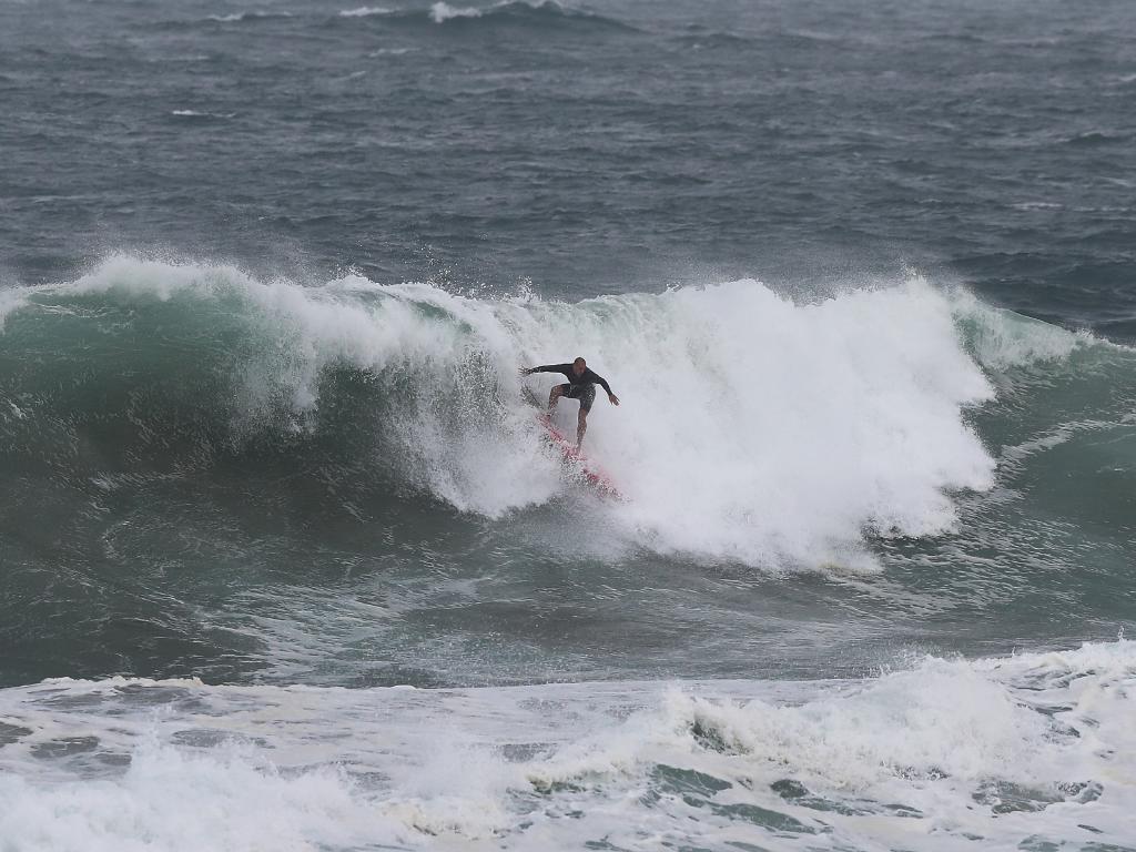 Wanda beach Lifeguards Matt Hollman ( jet ski ) and Pierre Caley ( surfer ) use wild surf conditions at Cronulla for training. Picture: Brett Costello