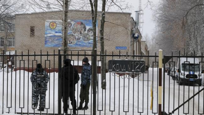 Russian police officers guard the entrance to a school after a knife incident in Perm, Russia. Picture: AP Photo/Alexander Agafonov
