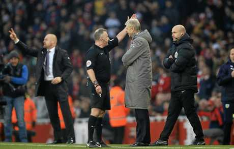 Arsene Wenger, centre right, confronts a referee.