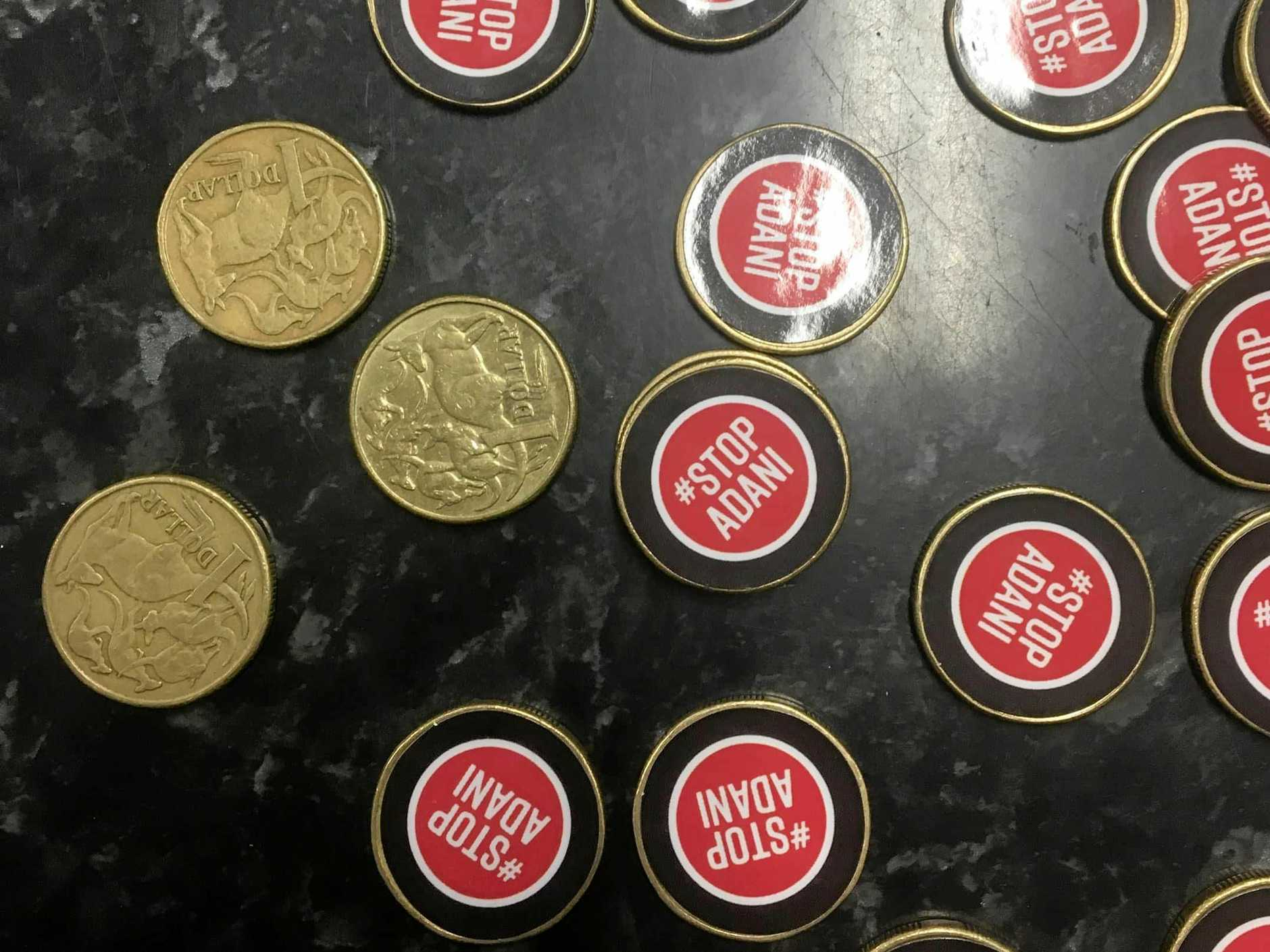 GETTING CREATIVE: Anti-Adani protesters have placed their stickers on $1 coins and handing them out in Bowen.