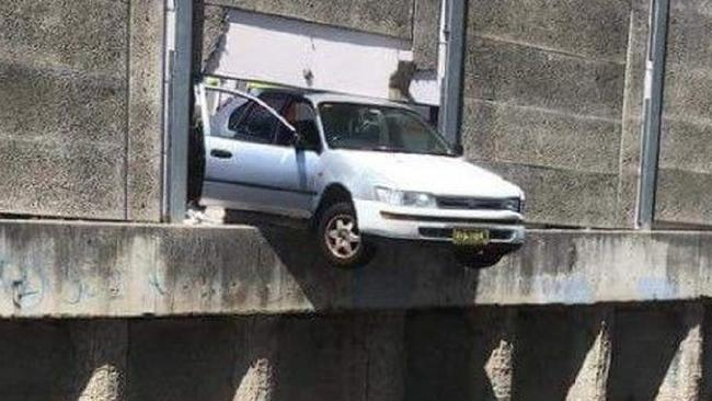A woman in her sixties  crashed her car through a wall, leaving her vehicle hanging precariously over the railway line at Sefton station. Pictures: 9 News