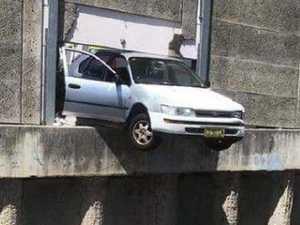 Car hangs perilously above train tracks
