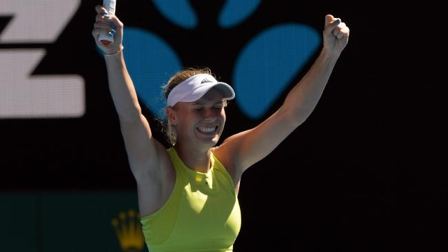 Caroline Wozniacki raises her arms in jubilation after surviving a huge scare against Jana Fett on Rod Laver Arena. Picture: AAP