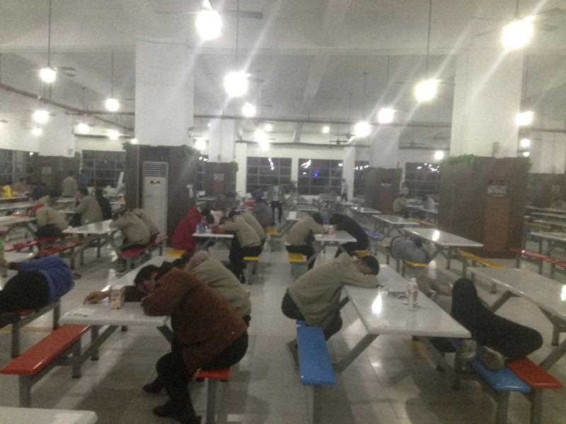 Factory workers rest at night in a cafeteria at a Catcher Technologies factory in Suqian in eastern China's Jiangsu province