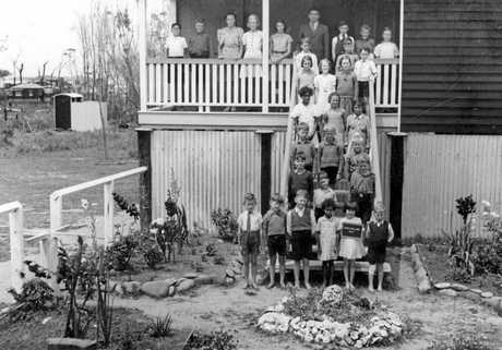 Mooloolaba State School principal Arthur Bray Parkyn standing on the verandah of the one-teacher school surrounded by pupils in 1940.