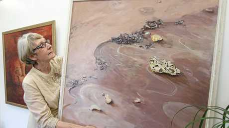 Cecilie Bolton hanging one of her works for the exhibition  A Second Look  at the Mill Gallery.