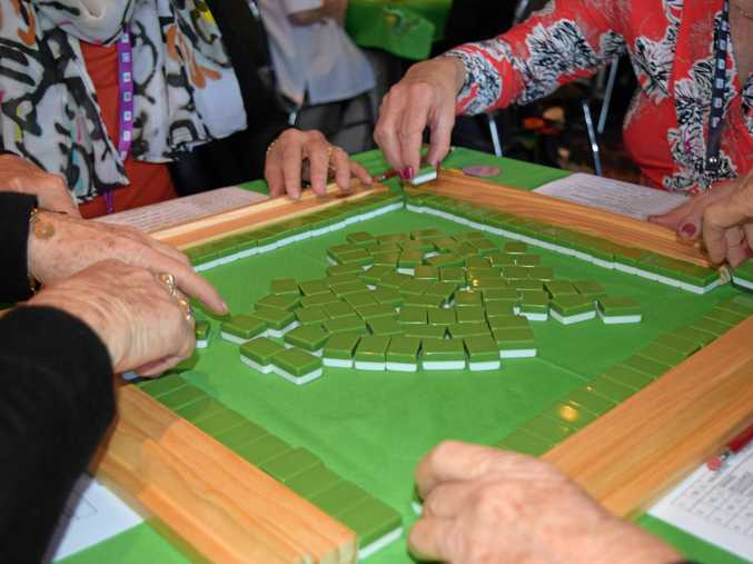 Players drawing hands for a fresh game of Mahjong.