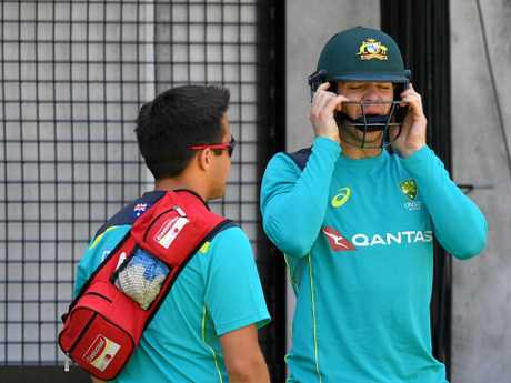 Tim Paine (right) gets ready for training at the Gabba.