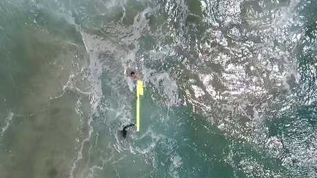 The surfers use the device to get back to shore as the drone watches on.
