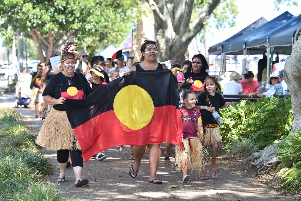 People from the local indigenous community march along the Esplanade calling for a change of date for Australia Day.