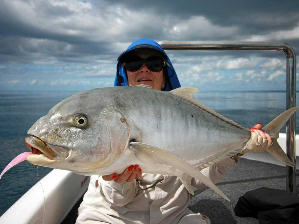 Michele from Hope Island with a solid golden trevally caught with Hervey Bay Fly and Sportfishing.