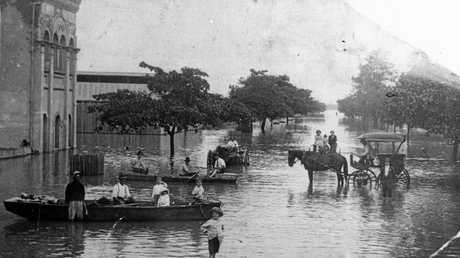 People go about thier business in East Street by boat, carriage and on foot during the 1918 flood.