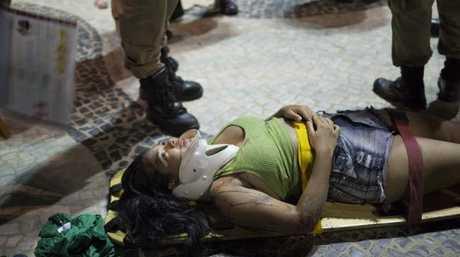 A woman lies on a stretcher waiting for an ambulance. Picture: AP Photo/Silvia Izquierdo
