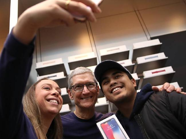 Apple Chief Executive Tim Cook, centre, poses for a selfie with customers during the debut of the iPhone X. Picture: Justin Sullivan