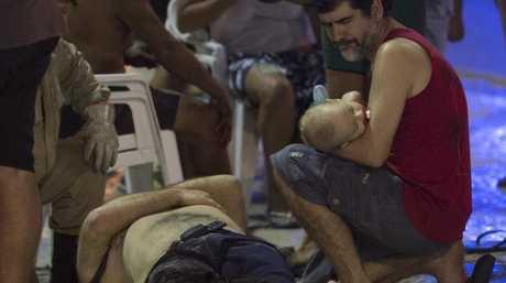 A man holds a baby next to an injured man in Rio de Janeiro, Brazil. Picture: AP Photo/Silvia Izquierdo
