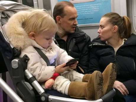 A baby girl is pictured playing with a mobile phone while riding on a New York subway. Photo: AP/Mark Lennihan