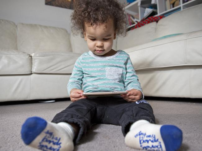 18-month-old Gabriel plays on an iPhone at his Doreen home. Photo: Nathan Dyer