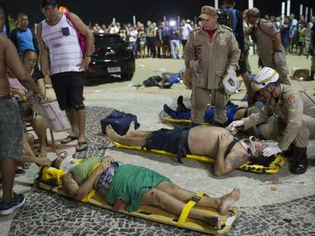 Firefighters give the first aid to people that were hurt after a car drove into the crowded seaside boardwalk along Copacabana beach in Rio de Janeiro, Brazil. Picture: AP Photo/Silvia Izquierdo