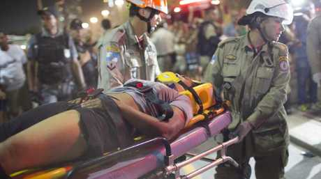 Firefighters carry a woman on a stretcher after a car drove into the crowded seaside boardwalk along Copacabana beach. Picture: AP Photo/Silvia Izquierdo