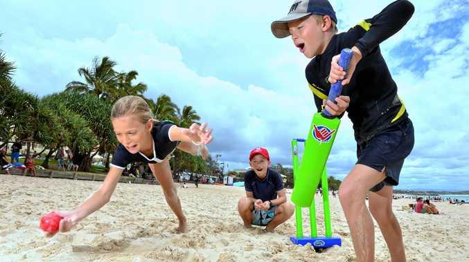 Molly Stoddart, 11, Joe Stoddart, 9, and Hugh Rylance, 9, of Brisbane, get stuck into some beach cricket on Main Beach, Noosa Heads.