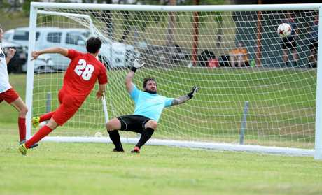 Southside United's Yianni Kondilis puts the ball past Wide Bay Buccaneers under-20 keeper Chris Merrison at Jardine Park on Saturday.