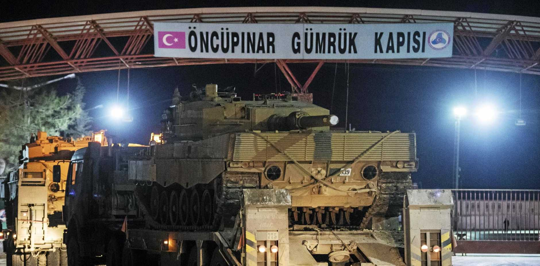 Turkish military trucks carrying tanks and other armoured vehicles cross through a border gate into a Turkish-controlled region of the Oncupinar border crossing with Syria.