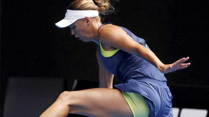 RARE ENOUGH: A confident Caroline Wozniacki hits the ball between her legs during her straight-sets win over Magdalena Rybarikova.