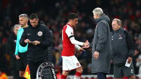 Mesut Ozil of Arsenal shakes hands with Arsene Wenger
