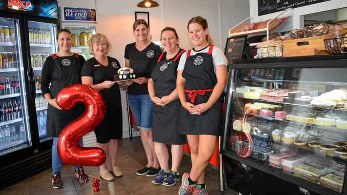 Keely Roberts and Simone Lawrie (middle with cake) with staff celebrating their second birthday.