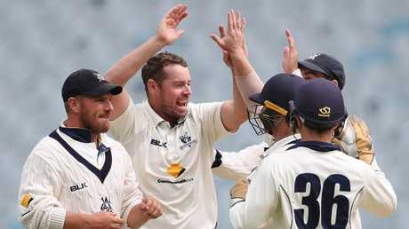 Jon Holland is congratulated by Aaron Finch and his Victorian teammates after a Sheffield Shield wicket in December. Picture: Scott Barbour/Getty Images