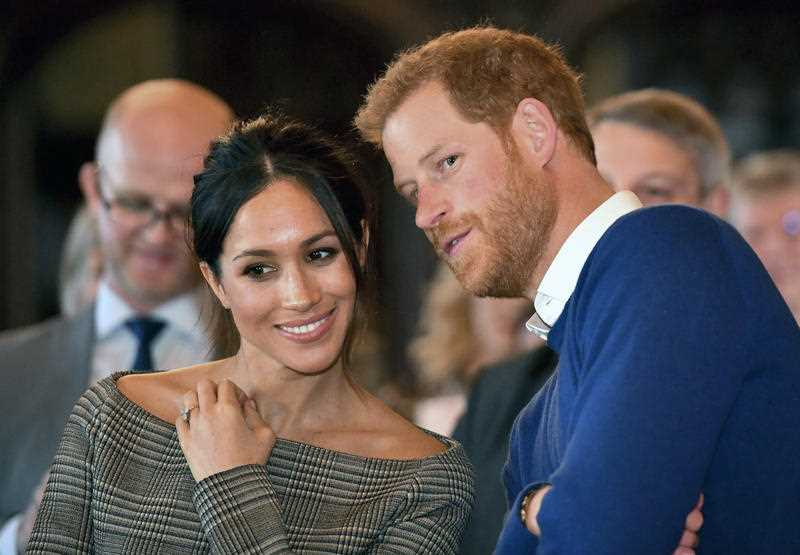 Britain's Prince Harry talks to Meghan Markle as they watch a dance performance