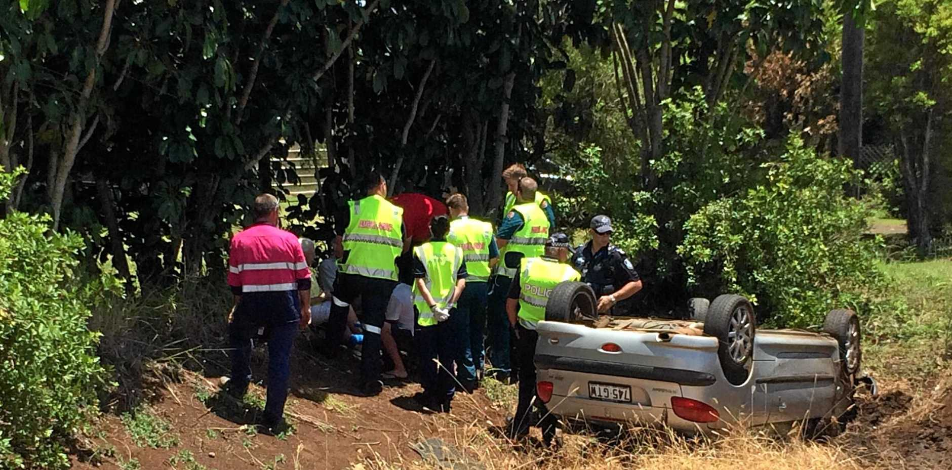 ROLLOVER: An elderly couple are being treated by paramedics are rolling their car down an embankment.