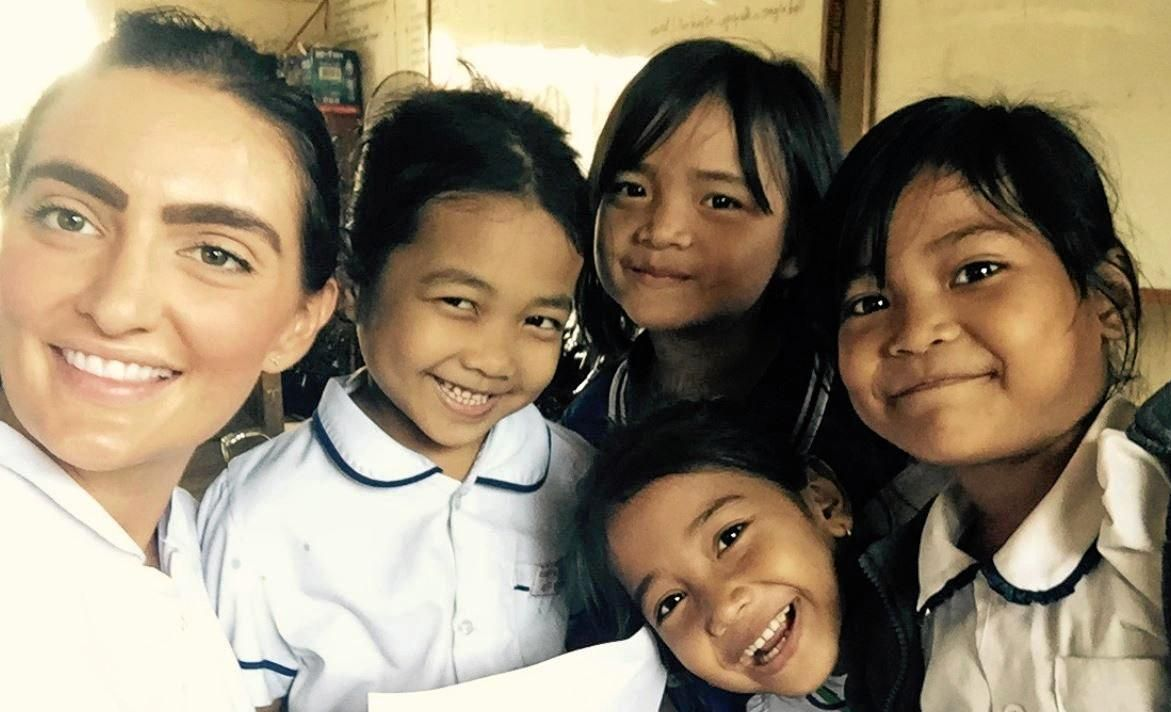 ALL SMILES: Former Fairholme College student and dentist Dr Sophie Bennett (left) and the school children from Cambodia she treated.