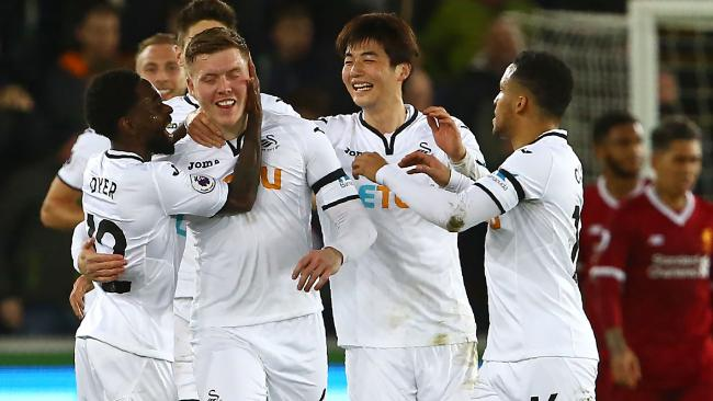 Swansea City's English defender Alfie Mawson (C) celebrates.