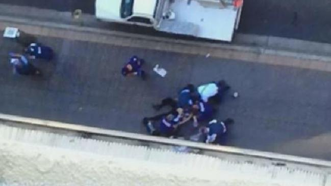 Paramedics and police officers around the body of NSW police worker Curtis Cheng, after he was shot dead.