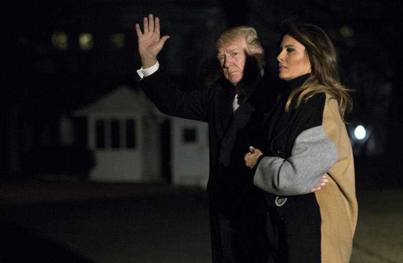 President Donald Trump with first lady Melania Trump waves as he returns to the White House in Washington