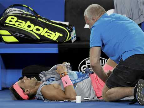 Rafael Nadal receives treatment before pulling out of the Australian Open.