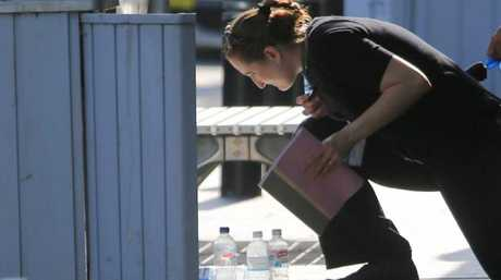 Police at the scene of the shooting, paid particular interest in the bins and water bottles. Picture: John Grainger