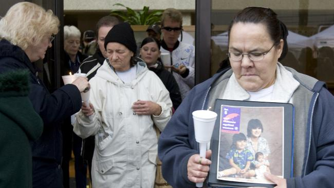 Daphane Pierre holds a picture of her sister Jackie Murdock and Jackie's children Ryan after Robert Pickton was found guilty on six counts of second-degree murder. Picture: AP Photo/Jonathan Hayward, CP
