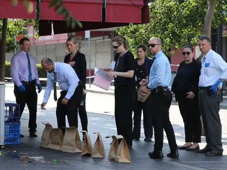 Detectives collect evidence at the murder scene today. Picture: John Grainger