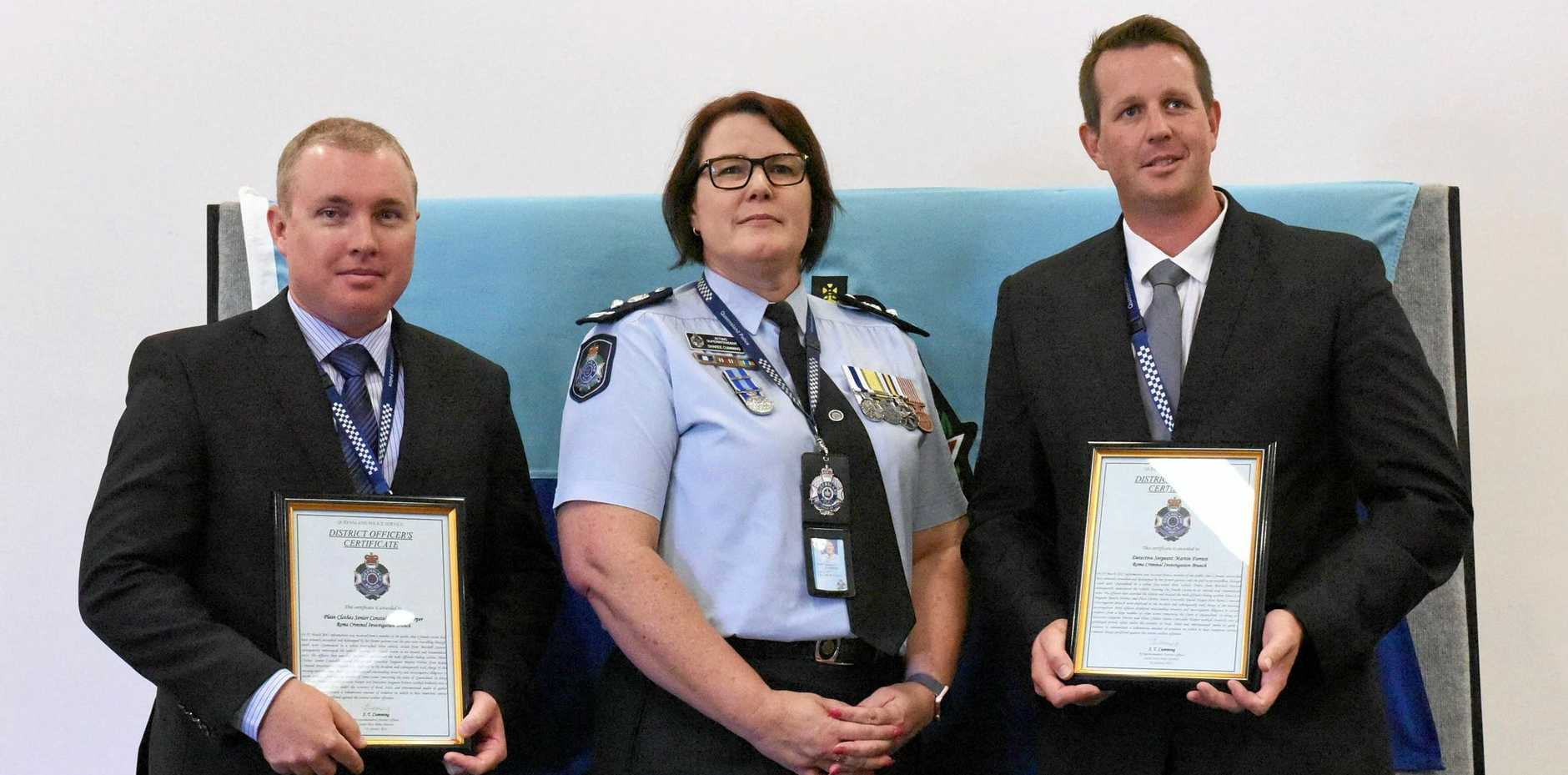 Detective Sergeant Martin Forrest and Detective Senior Constable David Harper receive the officer's certificate.
