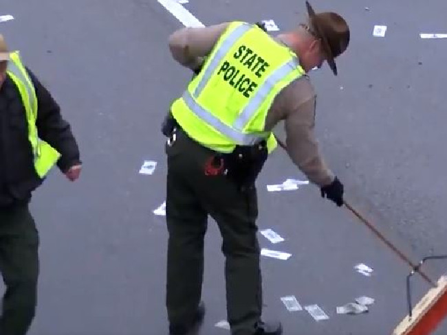 A policeman attempts to sweep up the spilt $5, $10 and $20 bills. Picture: Twitter/CNN